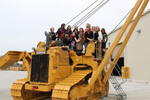 Several of PLM's staff pose on the new 72H pipelayer.