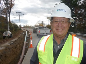 Summit Natural Gas of Maine President Michael Minkos stands beside a stretch of pipeline that is part of an effort to reach 52,000 customers in the next five years.