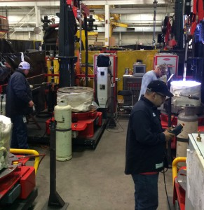 ValvTechnologies staff running parts for 8-inch 2500-pound valves on the compact cladding machines.